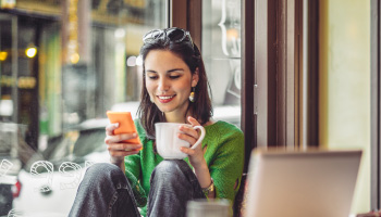 A young woman sitting in a cafe using a cell phone.